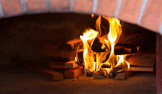 close up of fire burning wood inside the brick frame of a wood oven