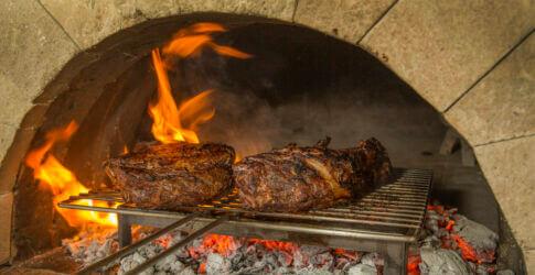 Gilling meat over coals in Mugnaini oven