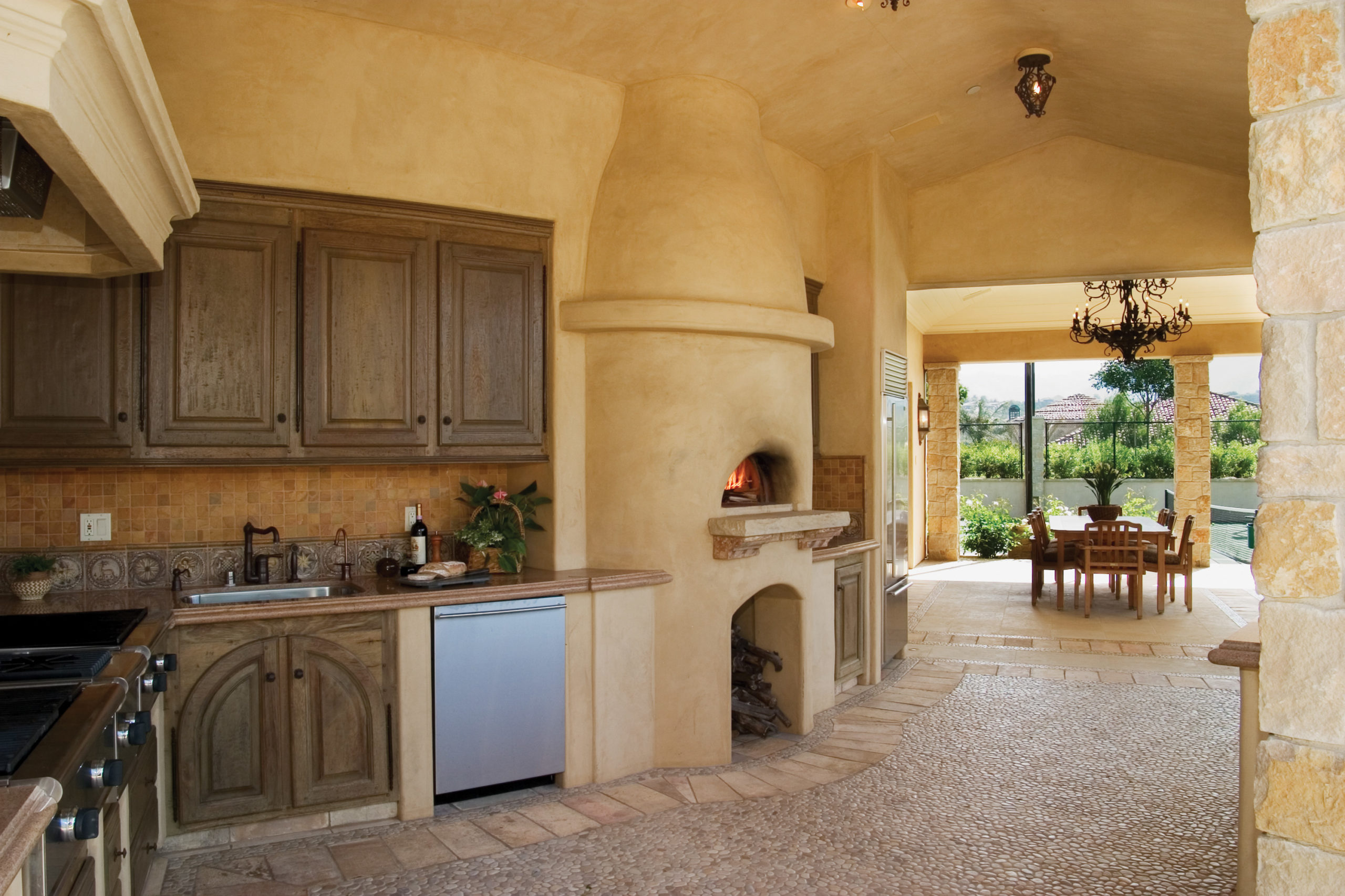 residential mediterranean style kitchen with Mugnaini wood oven