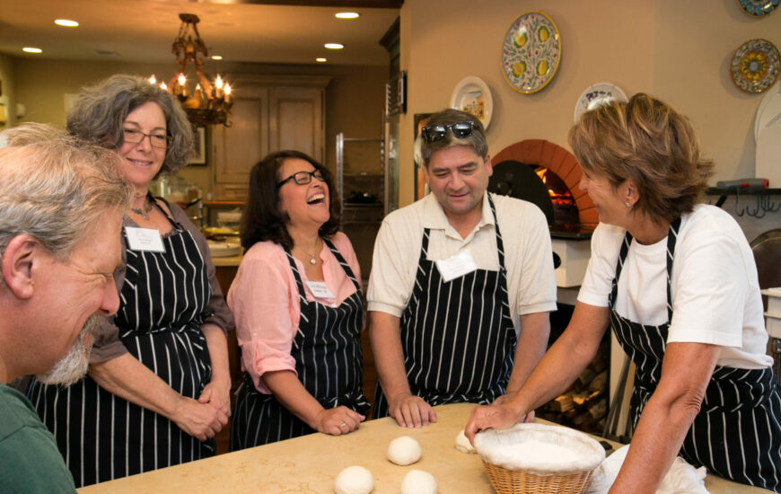 Andrea in kitchen teaching four students how to roll dough